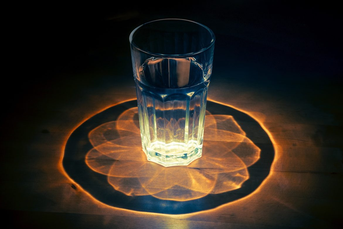 design created by light traveling through water glass
